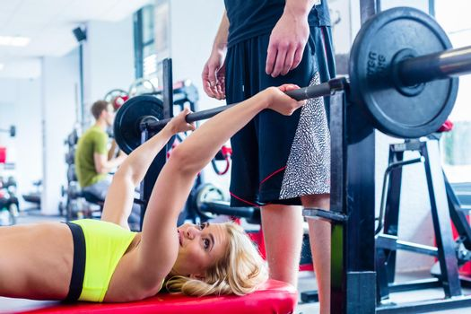 Woman with personal trainer at bench press in gym