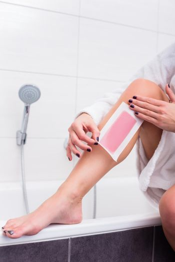 Woman using wax strips for depilation