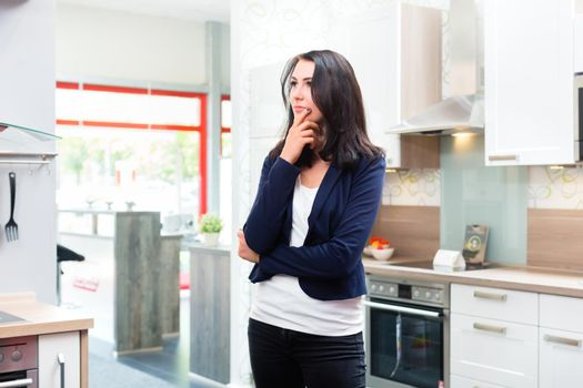 Woman buying domestic kitchen in furniture store