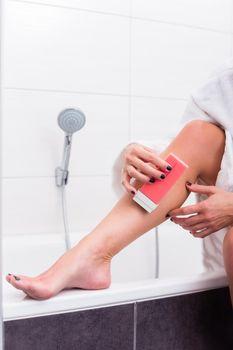 Woman applying epilation lotion on legs