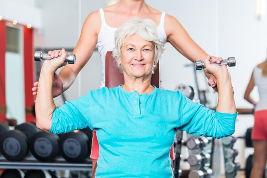 Senior woman with trainer in gym lifting dumbbell