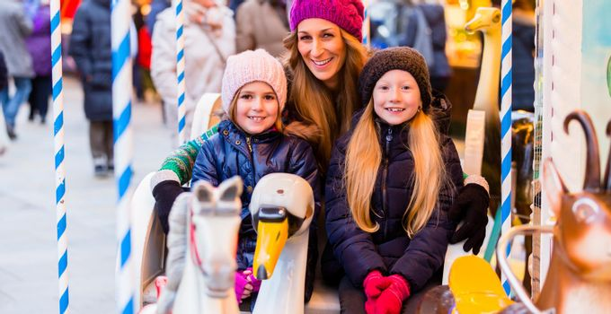 Family riding the carousel on Christmas market