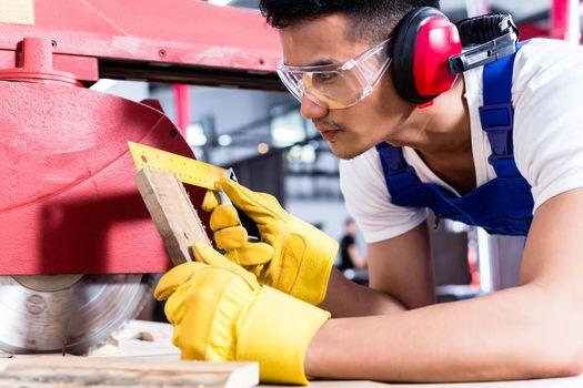 Carpenter in Asian workshop with circular saw
