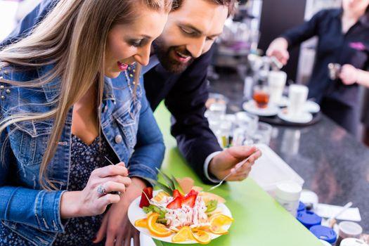 Woman eating fruit sundae in ice cream cafe
