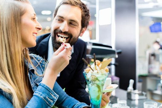 Couple enjoying an ice cream sundae in cafe