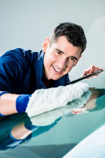 Cheerful young worker polishing car with soft microfiber mitt