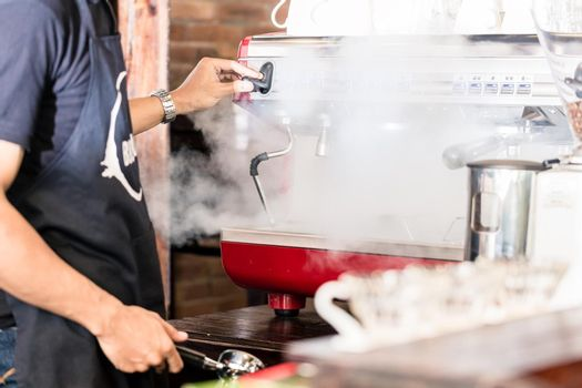 Barista preparing coffee at steaming machine in cafe