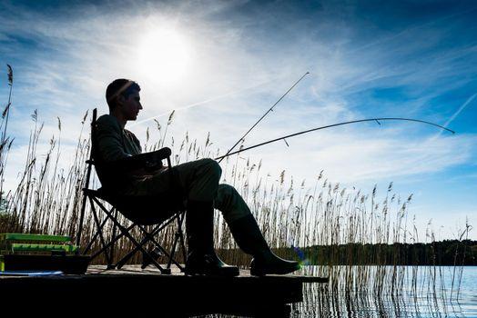 Fisherman or Angler at lake in Sunrise backlit