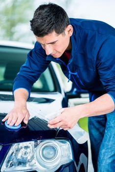 Happy man looking at camera while waxing a blue car