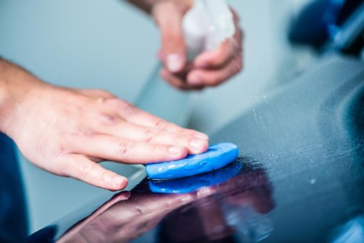 Close-up of male hands waxing a blue car at auto wash