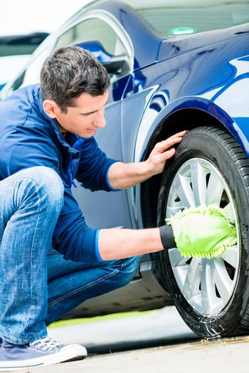 Worker using microfiber car wash mitt for cleaning rim