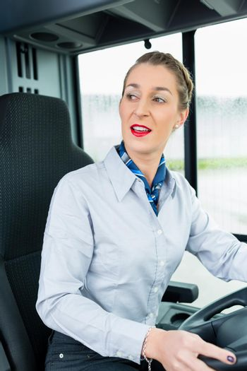 Female bus driver in drivers seat