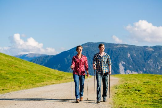 Couple doing nordic walking exercise in mountains