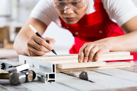 Asian Chinese Carpenter cutting wood with saw
