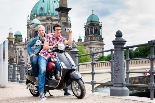 Couple taking a selfie during sightseeing tour with Vespa