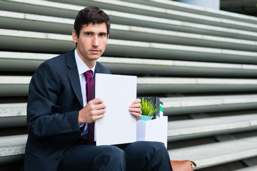 Young unemployed man sitting on stairs after being fired or after business bankruptcy