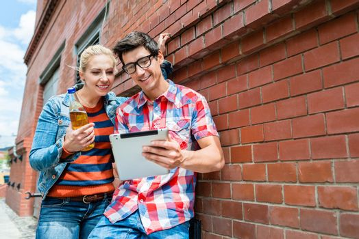 Couple on holidays organizing sightseeing tour with tablet PC