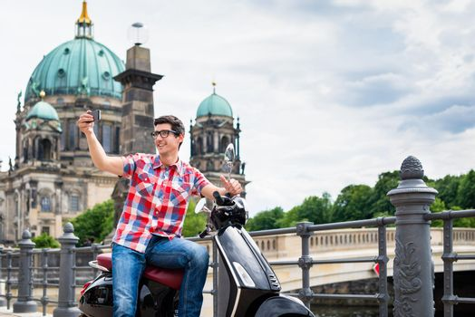man taking a selfie during sightseeing tour with Vespa