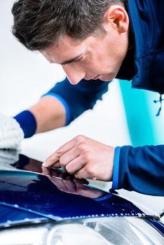 Hard-working man polishing car with white microfiber mitt