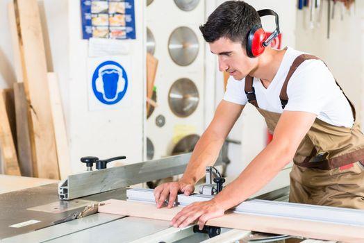 Carpenter cutting wooden plank in his workshop