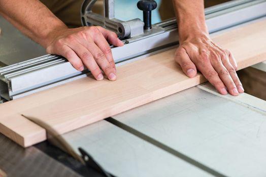 Carpenter cutting wooden board with circular saw