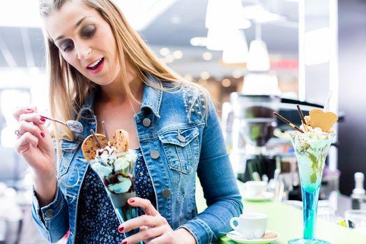 Woman eating amaretto sundae in ice cream cafe