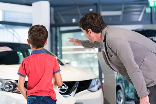 Father with son in car dealer showroom buying auto