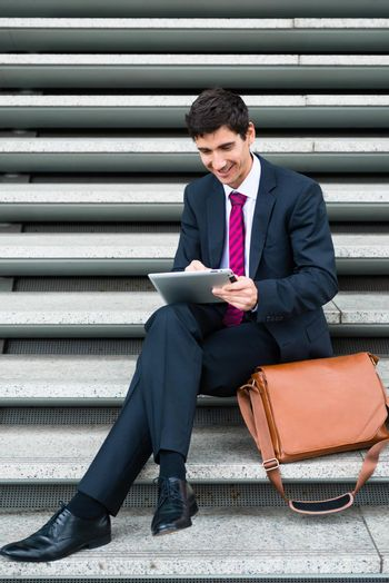 Young businessman smiling while using a tablet PC for online communication or data storage outdoors