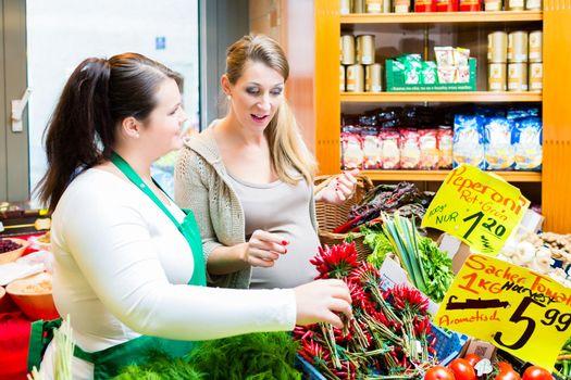 Customer and sales clerk in delicatessen store