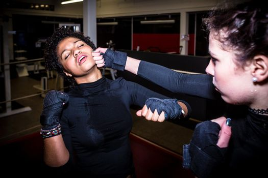 Tough female fighter punching her opponent in the face while pra