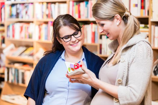 Two friends reading book in bookstore together