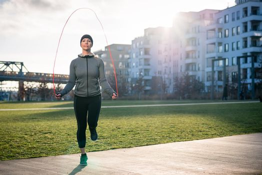 Young fit woman burning calories through alternate jumping