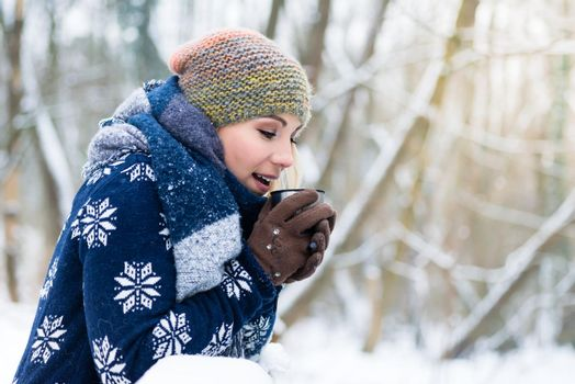 Woman freezing on a cold winter day warming herself up with hot