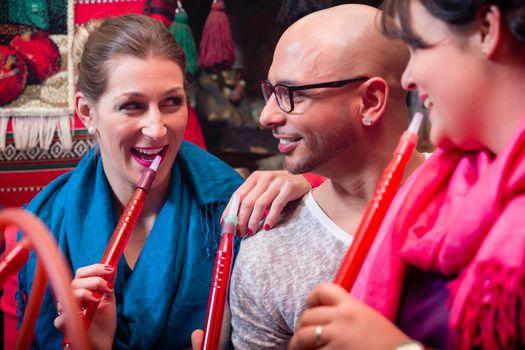 Women and man enjoying recreational shisha in hookah lounge