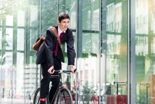 Cheerful young employee riding an utility bicycle in Berlin