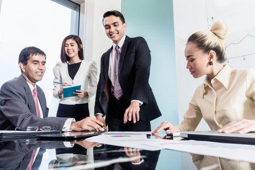 Group of businesswomen and businessmen negotiate contract