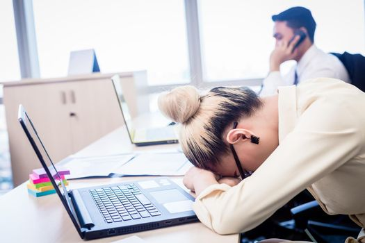 Young businesswoman taking nap in office