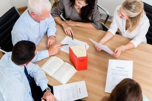 Lawyers in law firm reading documents and agreements