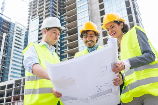 Architects with ground plot on construction site