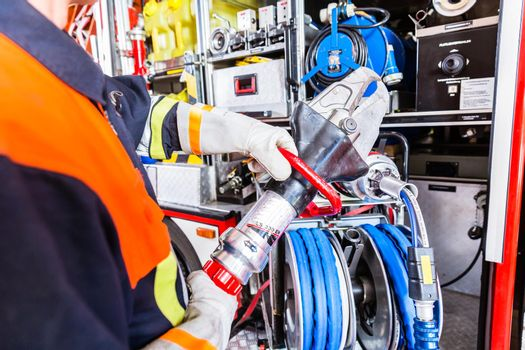 Fire fighter checking hydraulic cutter at fire engine