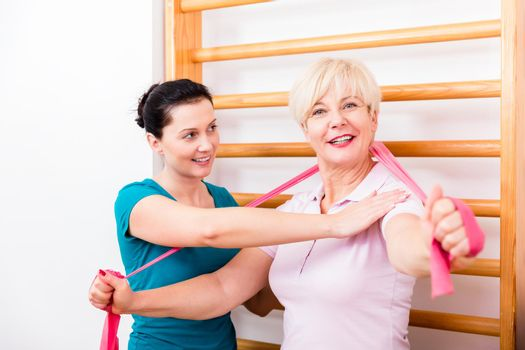 Physio assisting elderly woman during exercise with power band a