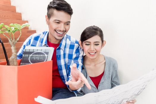 Asian couple with ground plot planning arrangement of new apartm