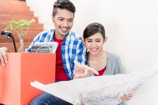 Asian couple with ground plot planning arrangement of new apartment