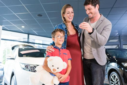 Family showing key to newly bought car in showroom