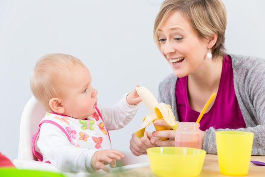 happy mother giving a fresh and nutritious banana to her cute baby girl
