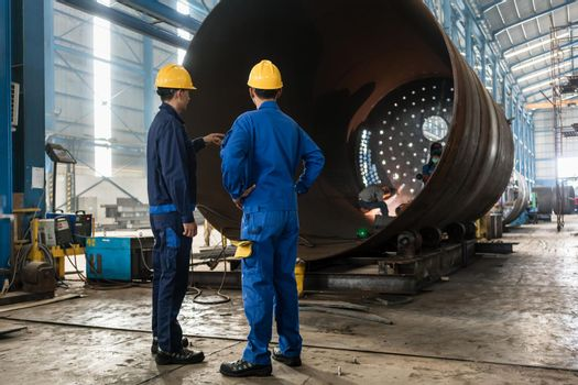 Workers supervising the manufacture of a metallic cylinder