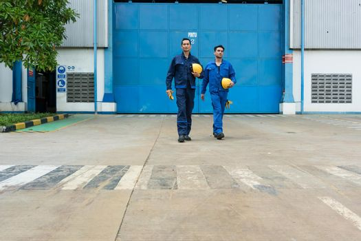 Two workers walking out from factory after work