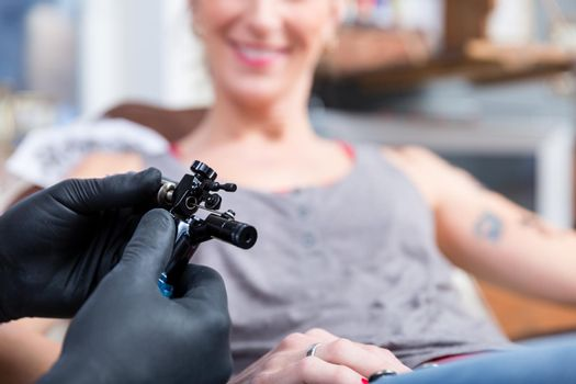 Hands of tattoo artist wearing sterile gloves
