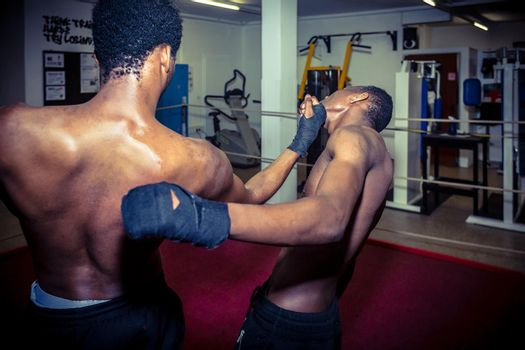 Two African American fighters practicing MMA takedown techniques in the ring