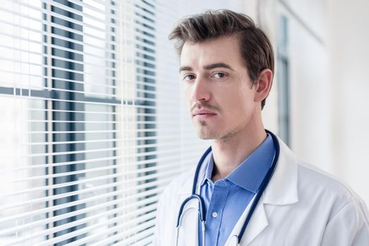Portrait of a young serious doctor looking at camera with determination